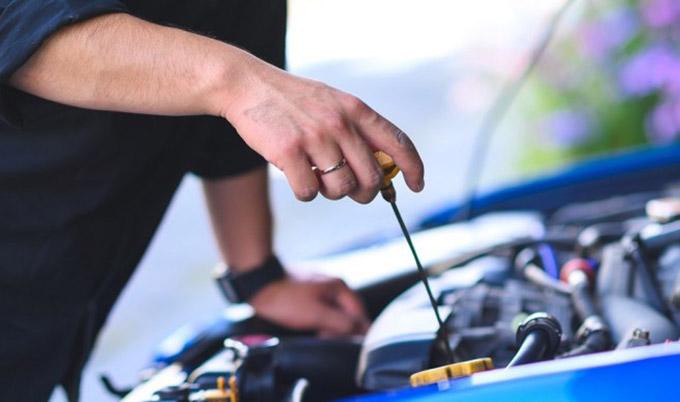 Un homme vérifie le niveau d'huile du moteur d'une voiture.
