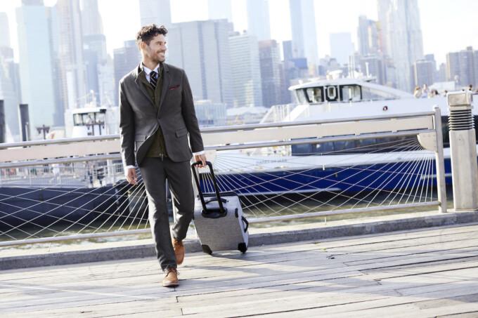 homme en costume roulant une valise derrière lui